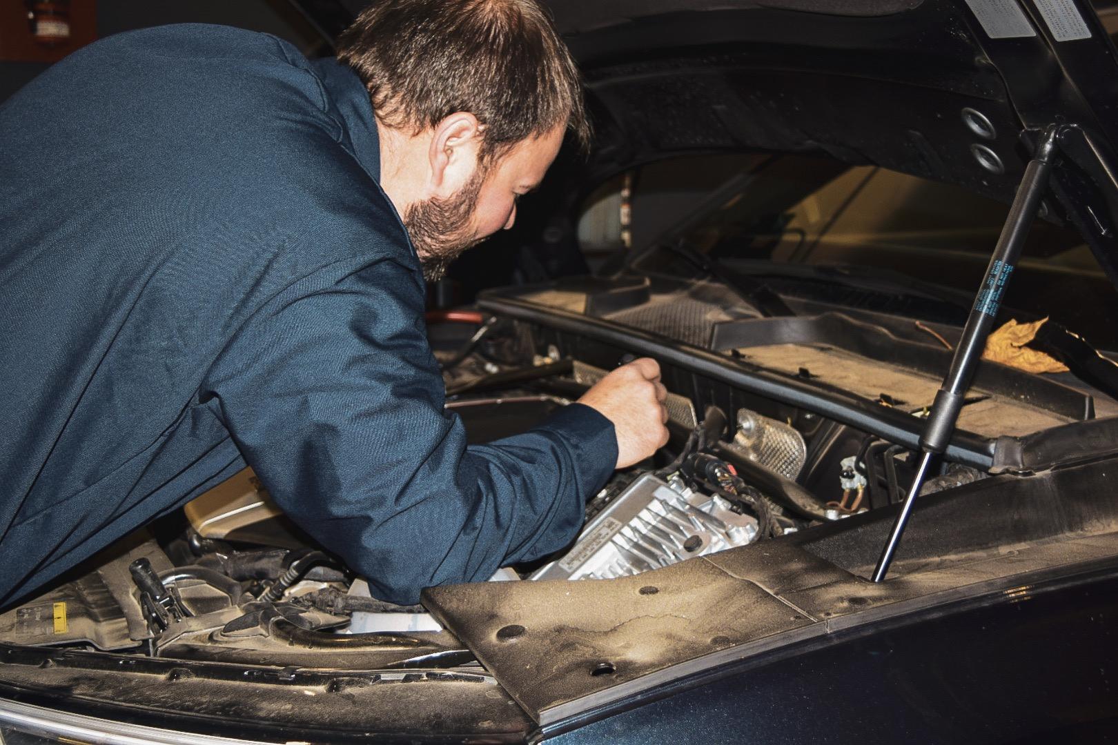 Employee working under the hood of vehicle